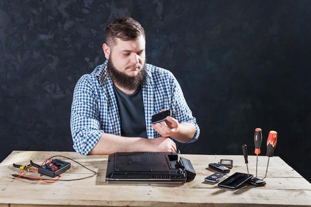 Männlicher computeringenieur, der problem mit laptop behebt. reparaturtechnologie für elektronische geräte