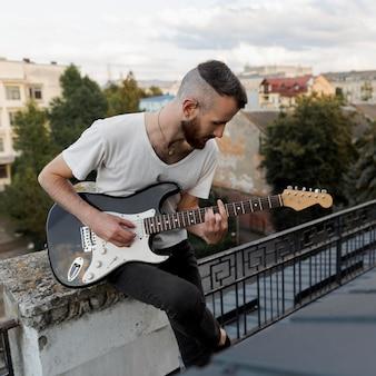 Männlicher darsteller auf dem dach, der e-gitarre spielt
