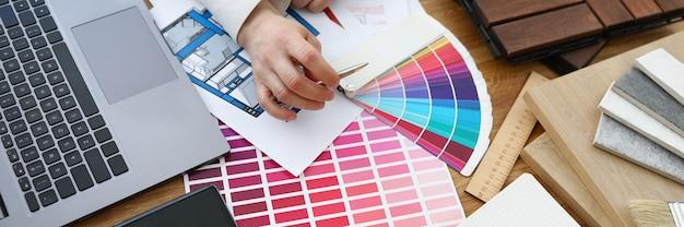 Männlicher designer-architekt wählt farben aus der farbpalette am arbeitsplatz aus