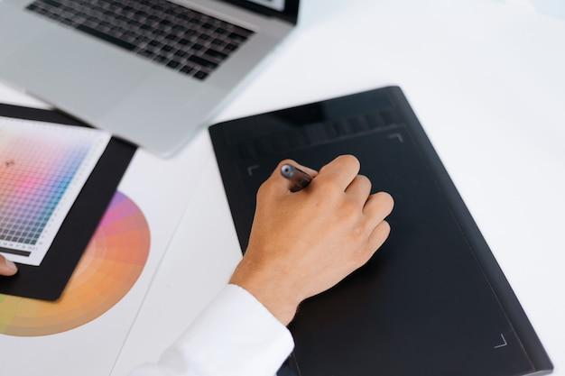 Männlicher designer, der ein grafiktablett verwendet, um mit der farbpalette zu arbeiten. mensch und technik.