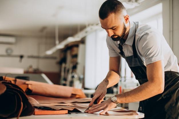 Männlicher designer und lederschneider, der in einer fabrik arbeitet