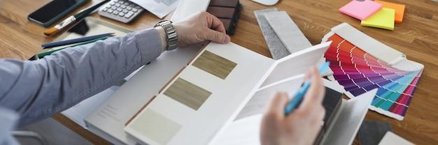 Männlicher designer wählt bodenbelagmuster für hausnahaufnahme