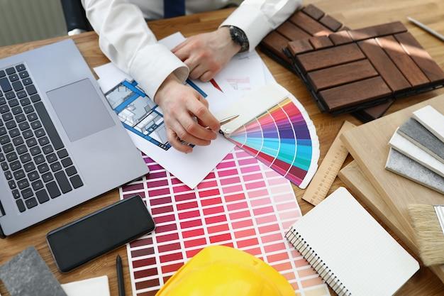 Männlicher designerarchitekt wählt farben aus der farbpalette am arbeitsplatz aus