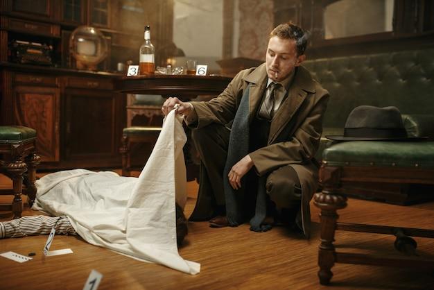 Männlicher detektiv im mantel, der am tatort auf die leiche des opfers schaut