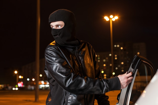 Männlicher dieb mit sturmhaube auf kopf, der autotür öffnet