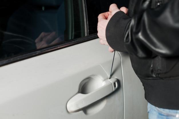 Männlicher dieb öffnet die autotür mit einem schraubenzieher