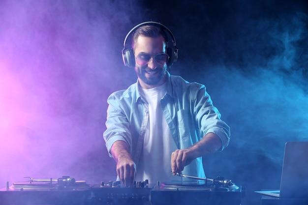 Männlicher dj, der musik im club spielt