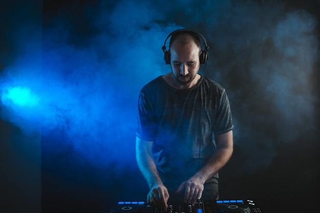 Männlicher dj, der unter den blauen lichtern arbeitet und in einem studio gegen eine dunkelheit raucht