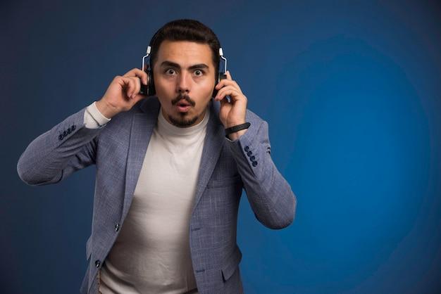 Männlicher dj im grauen anzug hört kopfhörer und wird überrascht.