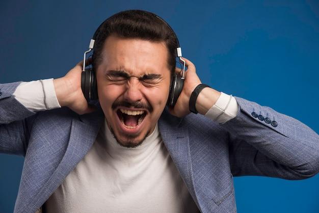 Männlicher dj im grauen anzug trägt kopfhörer mit hoher lautstärke und schreit.