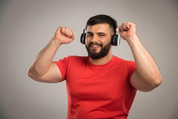 Männlicher dj im roten hemd, der kopfhörer trägt und musik beim tanzen hört