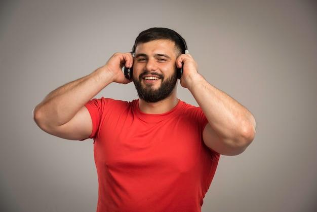 Männlicher dj im roten hemd, der kopfhörer trägt und musik hört.