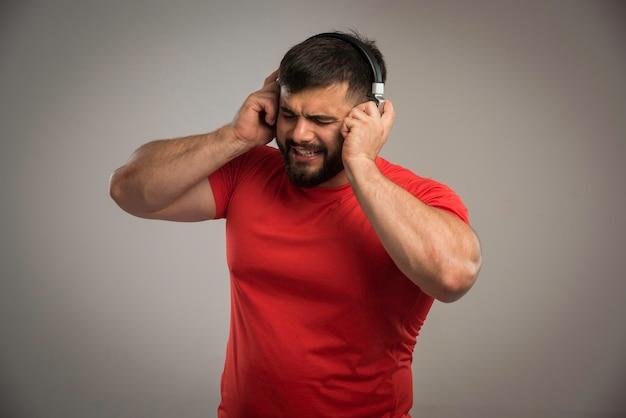 Männlicher dj im roten hemd, der kopfhörer trägt und singt.