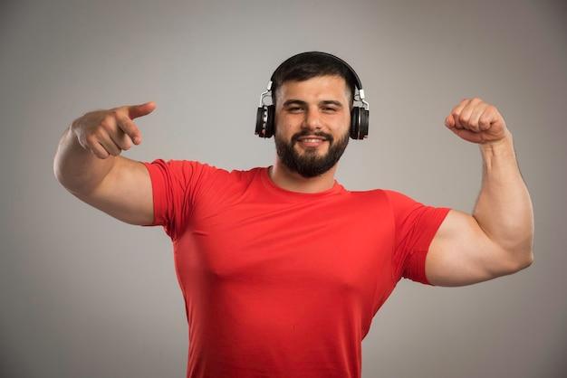 Männlicher dj im roten hemd, der kopfhörer trägt und tanzt.
