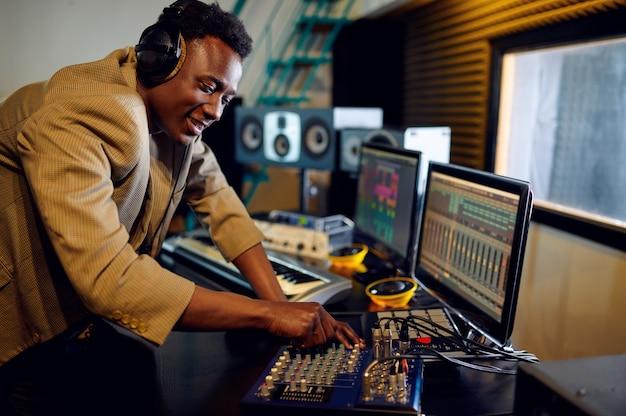 Männlicher dj in kopfhörern, der eine aufzeichnung am mischpult hört, aufnahmestudioinnenraum im hintergrund. synthesizer und audiomixer, musikerarbeitsplatz, kreativer prozess