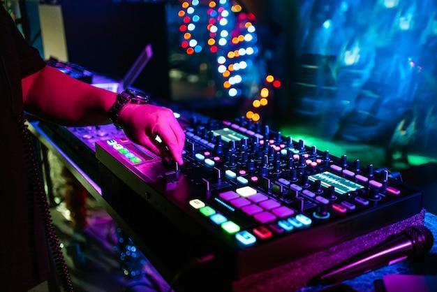 Männlicher dj mischt elektronische musik auf einem professionellen musikcontroller