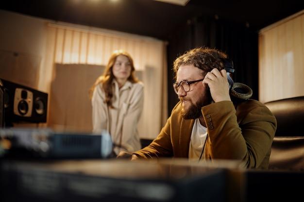 Männlicher dj und sängerin, aufnahmestudio-interieur im hintergrund. synthesizer und audiomixer, musikerarbeitsplatz, kreativer prozess