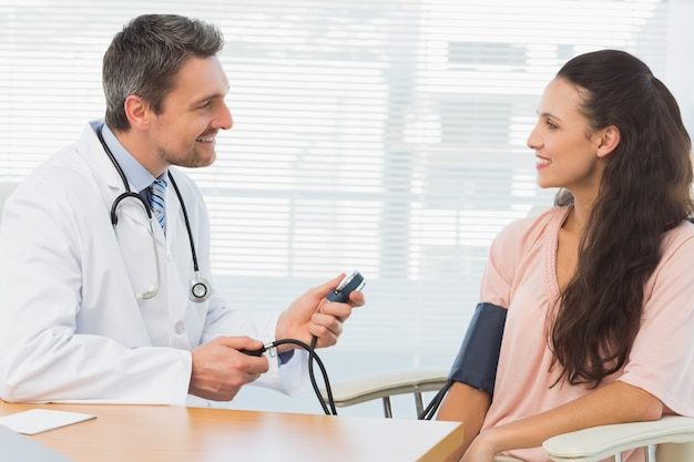 Männlicher doktor, der blutdruck einer jungen frau überprüft