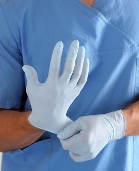 Männlicher doktor, der chirurgische handschuhe überzieht.