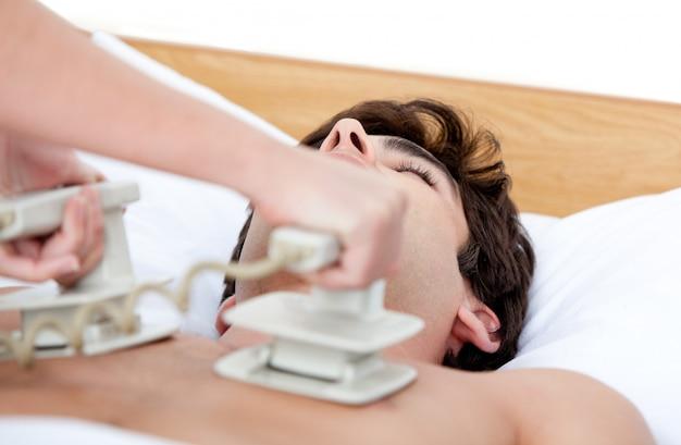 Männlicher doktor, der den defibrillator verwendet, um einen unachtsamen patienten wiederzubeleben