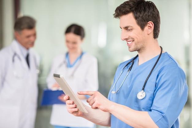 Männlicher doktor, der digitale tablette in der arztpraxis betrachtet.