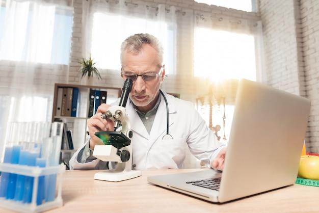 Männlicher doktor, der durch ein mikroskop in einem labor schaut.