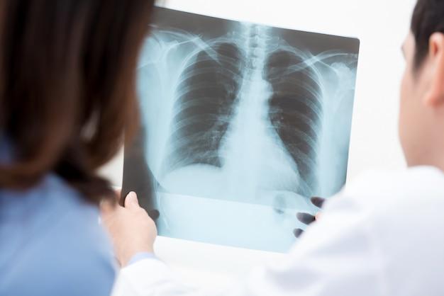 Männlicher doktor, der einem weiblichen patienten röntgenstrahl zeigt
