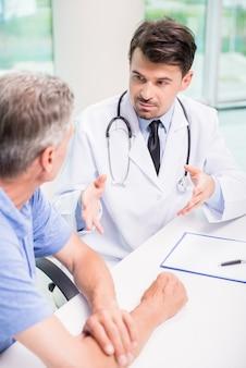 Männlicher doktor, der ernsthaft mit patienten an der klinik spricht.