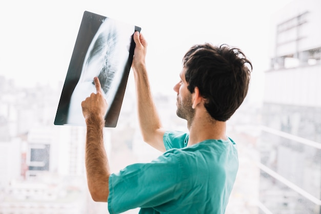 Männlicher doktor, der röntgenstrahl überprüft