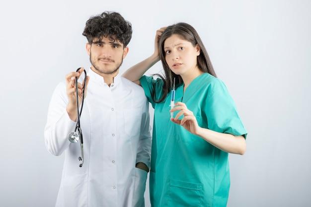 Männlicher doktor, der stethoskop nahe weiblicher krankenschwester hält, die spritze hält.