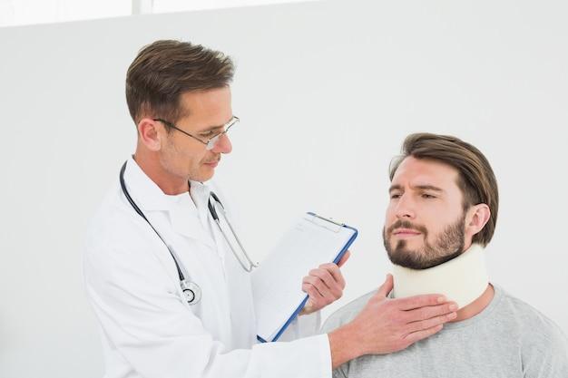 Männlicher doktor, der verstauchten hals eines patienten überprüft