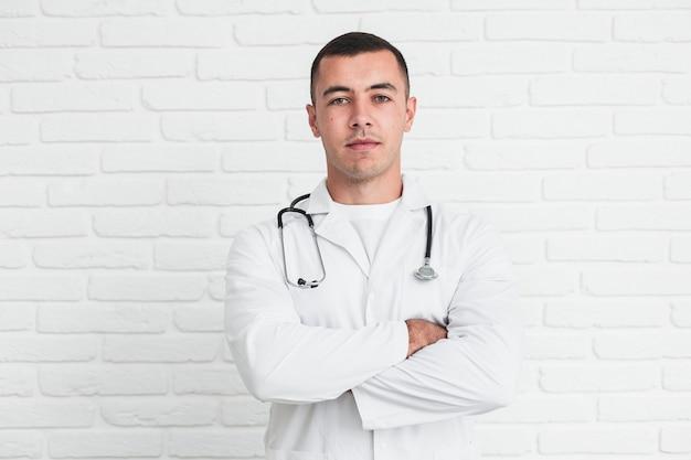 Männlicher doktor, der vor weißer backsteinmauer aufwirft
