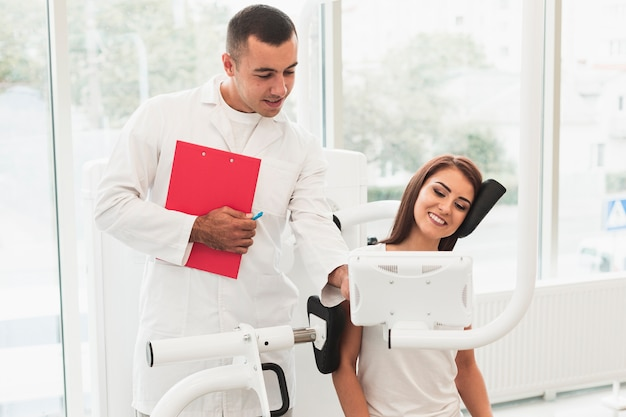 Männlicher doktor, der weiblichem patienten hilft