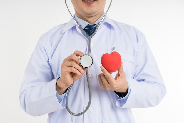 Männlicher doktor im weißen einheitlichen griff und gebrauchstethoskop, zum des roten spielzeugherzens des herzens zu überprüfen.