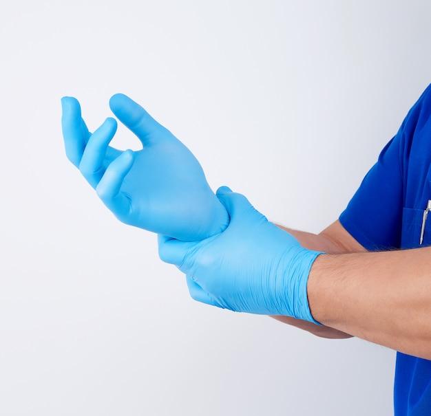 Männlicher doktor in der blauen uniform zieht seine hände weiße sterile latexhandschuhe an