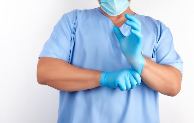 Männlicher doktor in der blauen uniform zieht seine hände weiße sterile latexhandschuhe vor chirurgie an