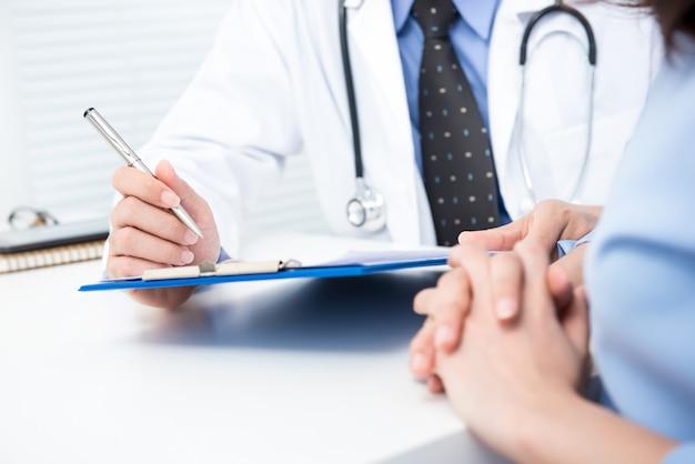 Männlicher doktor mit weiblichem patienten in der klinik