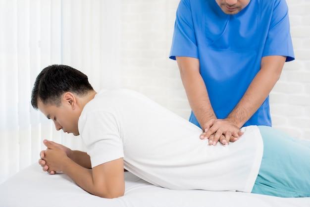 Männlicher doktortherapeut, der patienten der unteren rückenschmerzen in der klinik oder im krankenhaus behandelt