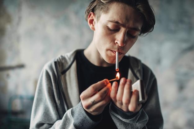 Männlicher drogenabhängiger zündet sich eine zigarette an