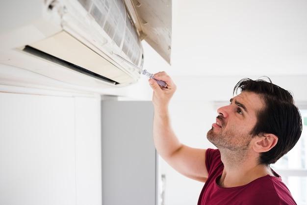 Männlicher elektriker, der klimaanlage durch tester überprüft