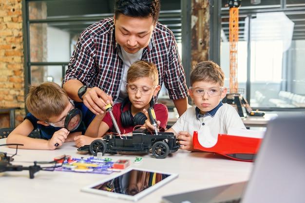 Männlicher elektronikingenieur mit europäischen schulkindern, die im intelligenten schullabor arbeiten und modell des ferngesteuerten elektroautos testen.