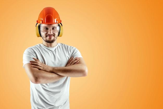Männlicher erbauer im orange sturzhelm auf einem orange hintergrund