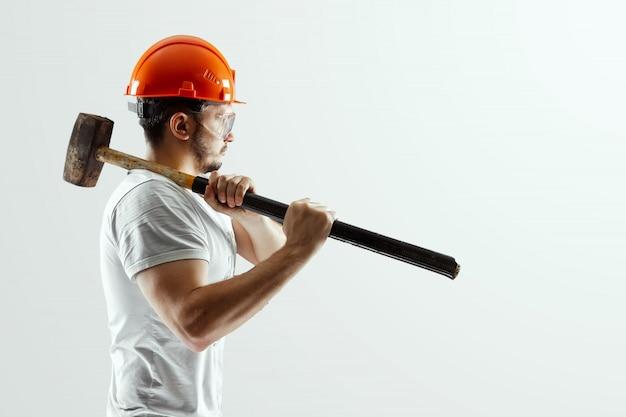 Männlicher erbauer im orange sturzhelm mit dem vorschlaghammer lokalisiert auf weißem hintergrund