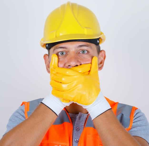 Männlicher erbauer in uniform, helm, handschuhe, die mund mit händen für fehler bedecken und schockiert schauen, vorderansicht.