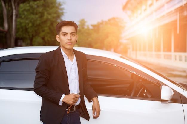 Männlicher erwachsener geschäftsmann in einer klage und halten eines autoschlüssels in seiner hand. weiße autos im hintergrund