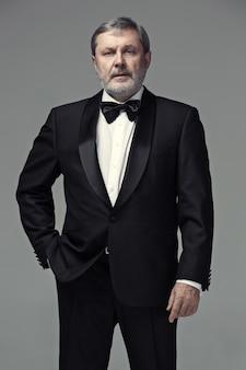 Männlicher erwachsener mittleren alters, der einen auf grau isolierten anzug trägt