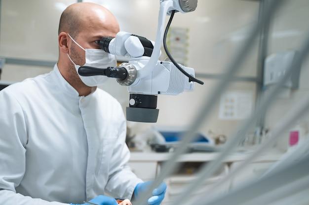 Männlicher fachmann in steriler maske untersucht das zahnmikroskop, während er den patienten im stuhl behandelt.