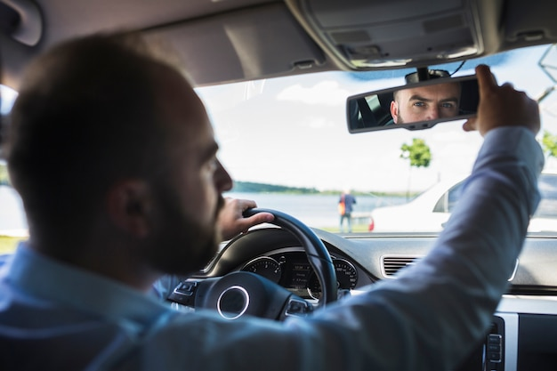 Männlicher fahrer, der hinteren spiegel des autos justiert