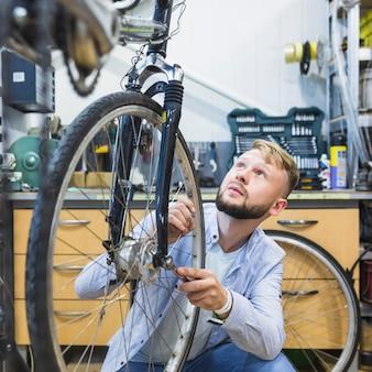 Männlicher fahrradmechaniker, der fahrradreifen im shop repariert