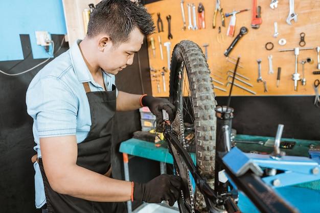 Männlicher fahrradmechaniker in der schürze, der die kette beim reparieren des problems am fahrrad schmiert
